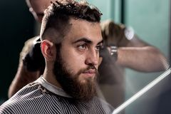Handsome young man with beard sits at a barber shop. Barber shaves hairs at the back. stock photo