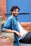 Handsome young man with beard sitting on step Stock Images