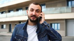 Handsome young man with beard is talking on the phone outdoors stock video