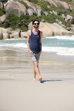Handsome young man with beard walking on isolated beach Royalty Free Stock Photography