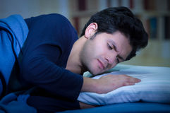 Handsome young man in bed with eyes opened suffering insomnia and sleep disorder fixing his pillow. Handsome young man in bed with eyes opened suffering Stock Photo