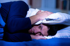 Handsome young man in bed with eyes opened suffering insomnia and sleep disorder thinking about his problem coverinh his. Head with a pillow, room background Stock Images