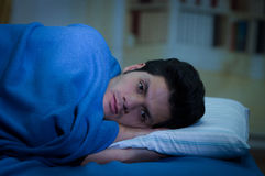 Handsome young man in bed with eyes opened suffering insomnia and sleep disorder thinking about his problem, room Stock Images