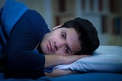Handsome young man in bed with eyes opened suffering insomnia and sleep disorder thinking about his problem, room. Background stock image