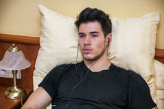 Handsome young man in bed listening to music Stock Photos