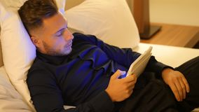 Handsome young man in bed typing on tablet PC stock footage