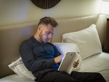 Handsome young man in bed typing on tablet PC. Sending text message or dialing number or reading web pages stock photography