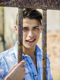 Handsome young man behind metal cage bars Stock Photos
