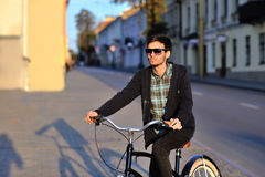 Handsome young man on a bicycle in city park Stock Photos