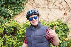 Handsome young man with bicycle showing thumbs up in park on sunny day stock images