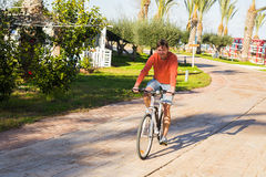 Handsome young man on bike in the park. Bicycle, leisure and people concept. Stock Images