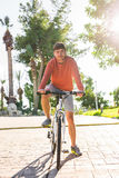 Handsome young man on bike in the park. Bicycle, leisure and people concept. Royalty Free Stock Image