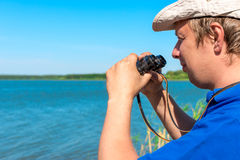 Handsome young man with binoculars Royalty Free Stock Photography
