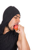 Handsome young man biting red apple Stock Image