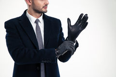 Handsome young man in black coat wearing leather gloves Stock Images