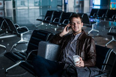 Handsome young man with black hair working, sitting on a chair things at the airport waiting for his flight Stock Image