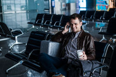 Handsome young man with black hair working, sitting on a chair things at the airport waiting for his flight Stock Photography