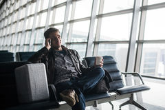 Handsome young man with black hair working, sitting on a chair things at the airport waiting for his flight Royalty Free Stock Image