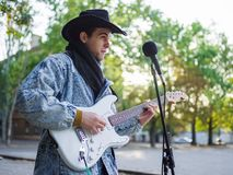 Young guy sings songs and plays guitar on a jeans jacket in a park on a natural background. Music concept. Handsome young man with a black hat plays the guitar stock photo