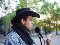Young guy sings songs and plays guitar on a jeans jacket in a park on a natural background. Music concept. Handsome young man with a black hat plays the guitar stock photography