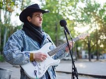 Young guy sings songs and plays guitar on a jeans jacket in a park on a natural background. Music concept. Handsome young man with a black hat plays the guitar royalty free stock photos