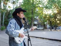 Young guy sings songs and plays guitar on a jeans jacket in a park on a natural background. Music concept. Handsome young man with a black hat plays the guitar royalty free stock photography