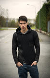 Handsome young man in black hoodie sweater outdoor in street Stock Photos