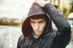Handsome young man in black hoodie sweater Stock Images