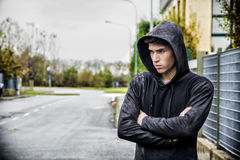 Handsome young man in black hoodie sweater standing outdoor Royalty Free Stock Photo