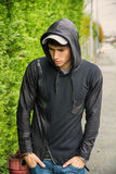 Handsome young man in black hoodie sweater standing outdoor Stock Photos