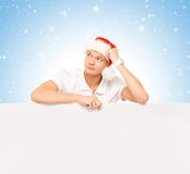Handsome young man with a blank billboard on a Christmas background Royalty Free Stock Photos