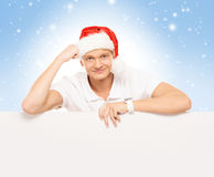 Handsome young man with a blank billboard on a Christmas background Stock Photography