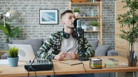 Handsome young man blogger recording audio talking in microphone in studio. Handsome young man blogger is recording audio talking in microphone in studio stock video footage