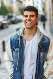 Handsome young man with blue eyes posing near a wall Stock Photography