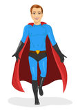 Handsome young man in blue superhero costume walking forward Royalty Free Stock Image
