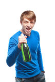 Handsome young man in a blue sweater with a bottle of champagne Royalty Free Stock Photography