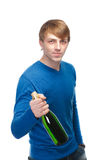 Handsome young man in a blue sweater with a bottle of champagne Stock Photography