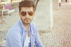 Handsome young man in bluejeans. Outside on the street royalty free stock photos