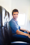 Handsome young man on board of an airplane during flight Royalty Free Stock Image