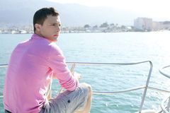 Handsome young man on boat, summer vacation stock photos