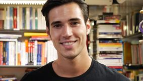 Handsome young man in bookstore smiling