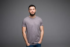 Handsome young man,boy,posing in grey shirt and jeans with hands in pockets on grey. Handsome young man,boy,posing in grey shirt and jeans with hands in pockets royalty free stock images