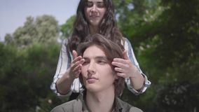 Portrait handsome young man with braces and long hair sitting in the foreground, his girlfriend comes from behind and. The handsome young man with braces and stock footage