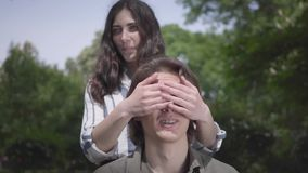 The handsome young man with braces and long hair sitting in the foreground, his girlfriend comes from behind and. Covering his eyes. The guy looks up at her stock video footage