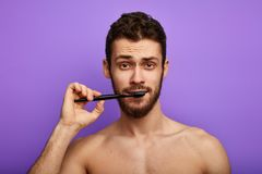 Handsome young man brushing teeth over blue background stock photo