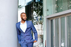 Handsome young man in business suit leaning against wall outdoors Royalty Free Stock Images