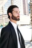 Handsome young man in business suit walking in the city Stock Photos