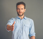 Handsome young man. Handsome young businessman in shirt is stretching his hand for greeting, looking at camera and smiling, on gray background Royalty Free Stock Photography