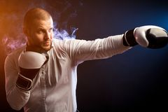 Man in suit. Handsome young man businessman in white shirt and black and white boxing gloves boxing in front of red and blue smoke from a wipe on a black stock photos
