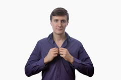 Handsome young man buttoning his violet shirt on white background Stock Photos